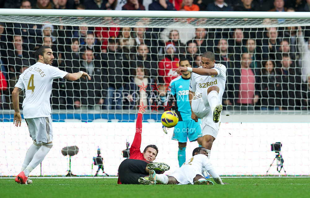 SWANSEA, WALES - Sunday, December 23, 2012: Swansea City's captain Ashley Williams clears the ball as Manchester United's Robin van Persie lies on the floor during the Premiership match at the Liberty Stadium. (Pic by David Rawcliffe/Propaganda)