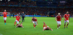 LILLE, FRANCE - Friday, July 1, 2016: Wales' captain Ashley Williams, David Cotterill, Andy King, Aaron Ramsey and Jonathan Williams slide on the pitch as they celebrate after a 3-1 victory over Belgium and reaching the Semi-Final during the UEFA Euro 2016 Championship Quarter-Final match at the Stade Pierre Mauroy. (Pic by David Rawcliffe/Propaganda)