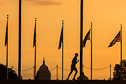 A runner passes flags around the Washington Monument silhouetted by sunset in Washington, DC.
