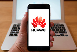 Using iPhone smartphone to display logo of Huawei, Chinese networking and telecommunications equipment and services company