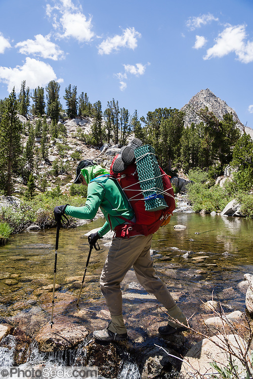 A backpacker crosses the outlet of Lower Lamarck Lake in John Muir Wilderness, Inyo National Forest, Sierra Nevada, California, USA. In the Bishop Creek watershed, enjoy a scenic hike from North Lake to Lamarck Lakes. The moderate trail to Upper Lamarck Lake is 5.5 miles round trip with 1550 feet cumulative gain. For licensing options, please inquire.