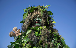 © Licensed to London News Pictures. 05/05/2018. Chalton, UK. A visitor to the Beltain Festival at Butser Ancient Farm dresses in green foliage with attendant squirrel. Over two thousand people have gathered to witness the ancient Beltain Celtic celebration of summer - which culminates in the burning of the giant Wickerman.  Photo credit: Peter Macdiarmid/LNP