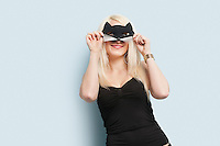 Portrait of a young woman wearing eye mask over light blue background