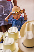A young boy tries on a cowboy hat at the Sunday market in Tlacolula de Matamoros, Mexico. The regional street market draws thousands of sellers and shoppers from throughout the Valles Centrales de Oaxaca.