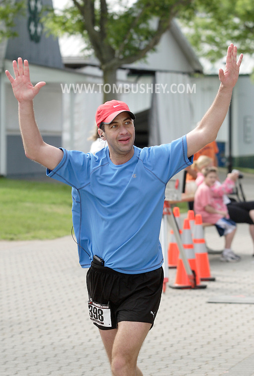 Augusta, New Jersey - Shiran Kochavi raises his arms as the starts one of his final laps during  the 3 Days at the Fair races at the Sussex County Fairgrounds on May 16, 2010. Kochavi won the men's 24-hour race.