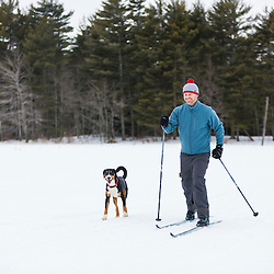 A man cross country skiing with his dog on a frozen pond in Epping, New Hampshire.