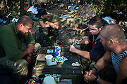 In the early morning, soldiers are sitting around a table discussing the enemy's movements on the frontline of Hranitne, near Mariupol, southeast Ukraine.