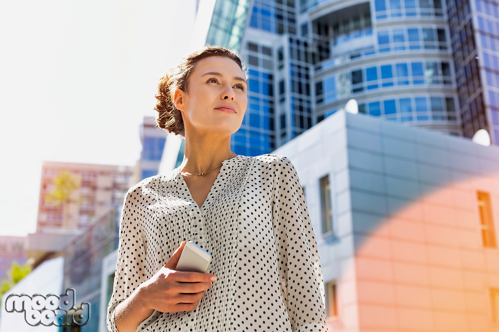 Portrait of young attractive woman holding smartphone while standing against office building with lens flare