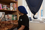 A prisoner looks at pictures of friends and family on display in her cell. HMP Send, closed female prison. Ripley, Surrey.