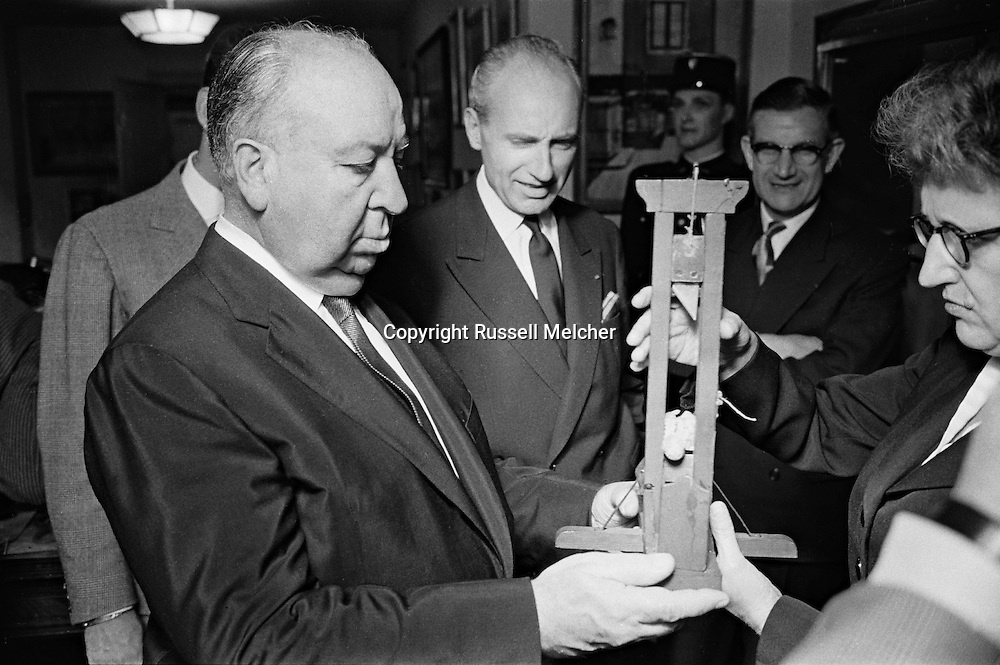 Alfred Hitchcock and the Head of Police (Prefet) examining a piece from the Crime museum,which are parts of famous crimes committed in France. <br />