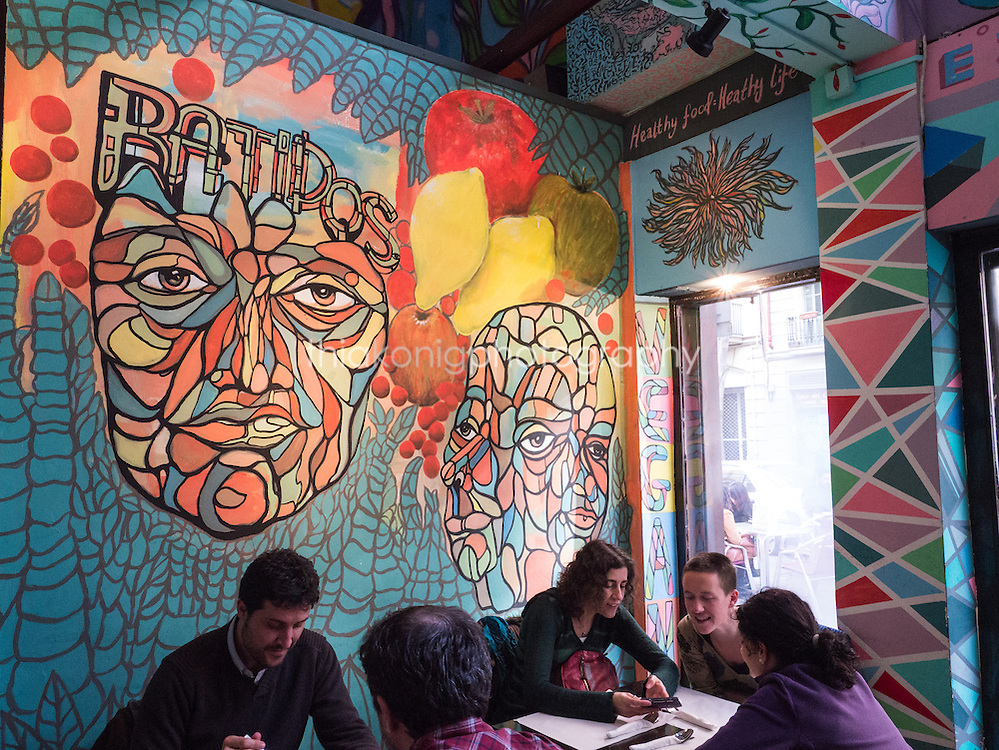 People sit under large wall mural at vegetarian restaurant in Barcelona, Spain.