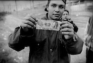 Migrant man from Honduras shows off his national currency as he waits for a frieght train to hop further north toward the US border, Lecheria train depot, Mexico City, Mexico.