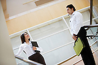 Business woman and business man talking on stairs