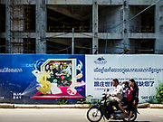"13 FEBRUARY 2019 - SIHANOUKVILLE, CAMBODIA: A Cambodian family on a motorcycle passes Blue Bay resort and casino, a new resort being built by Chinese investors in Sihanoukville. There are about 80 Chinese casinos and resort hotels open in Sihanoukville and dozens more under construction. The casinos are changing the city, once a sleepy port on Southeast Asia's ""backpacker trail"" into a booming city. The change is coming with a cost though. Many Cambodian residents of Sihanoukville  have lost their homes to make way for the casinos and the jobs are going to Chinese workers, brought in to build casinos and work in the casinos.      PHOTO BY JACK KURTZ"