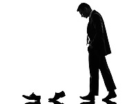 one caucasian business man walking behind his shoes  in silhouette on white background