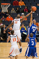 Virginia forward Jamil Tucker (12) battles with Hampton forward Donte Harrison (31) for a rebound.  The Virginia Cavaliers defeated the Hampton Pirates 74-48 at the John Paul Jones Arena on the Grounds of the University of Virginia in Charlottesville, VA on December 23, 2008. (Special to the Daily Progress / Jason O. Watson)
