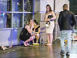 © Licensed to London News Pictures . 01/01/2015 . Manchester , UK . Woman crouch and eat a takeaway outside the Printworks on Withy Grove . Revellers usher in the New Year on a night out in Manchester City Centre .  Photo credit : Joel Goodman/LNP