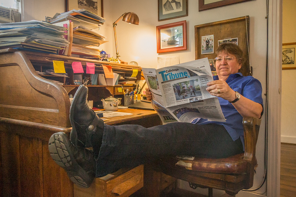 Editor Pat Hampton reads today's paper at her desk at the Calistoga Tribune offices.