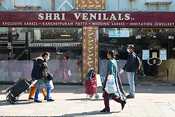 © Licensed to London News Pictures. 22/04/2020. London, UK. People wearing a face masks walk past closed shops and businesses in Ealing Road, Alperton. The start of the Muslim observation of Ramadan will begin during the Coronavirus lockdown.  Photo credit: Ray Tang/LNP