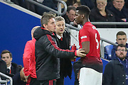 Kieran McKenna first team coach gives advice to Manchester United Midfielder Paul Pogba with Manchester United interim Manager Ole Gunnar Solskjaer looking on during the Premier League match between Cardiff City and Manchester United at the Cardiff City Stadium, Cardiff, Wales on 22 December 2018.