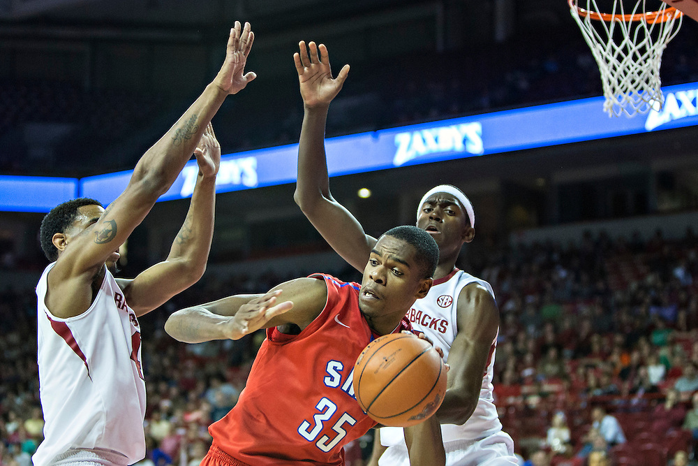 FAYETTEVILLE, AR - NOVEMBER 18:  Yanick Moriera #35 of the SMU Mustangs dribbles around two defenders during a game against the Arkansas Razorbacks at Bud Walton Arena on November 18, 2013 in Fayetteville, Arkansas.  The Razorbacks defeated the Mustangs 89-78.  (Photo by Wesley Hitt/Getty Images) *** Local Caption *** Yanick Moriera