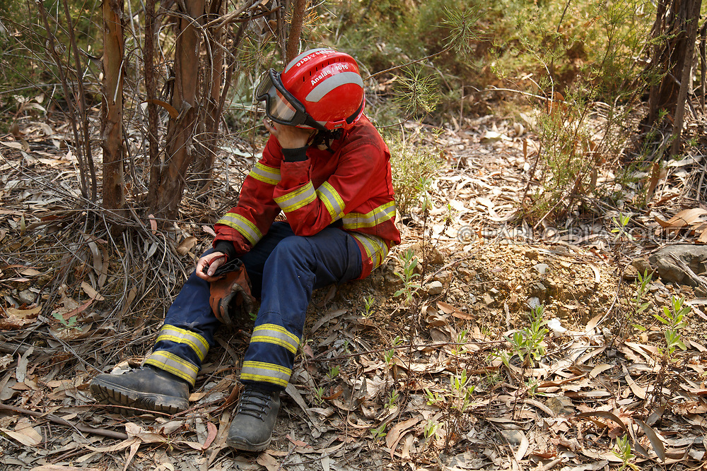 LEIRIA, PORTUGAL - JUNE 20:  A female firefighter takes a rest as she prepares to battle approaching flames after a wildfire took dozens of lives on June 20, 2017 near Picha, in Leiria district, Portugal. On Saturday night, a forest fire became uncontrollable in the Leiria district, killing at least 62 people and leaving many injured. Some of the victims died inside their cars as they tried to flee the area.  (Photo by Pablo Blazquez Dominguez/Getty Images)