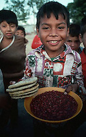 January 1983, San Salvador, El Salvador --- A refugee Salvadoran boy holds tortillas and a bowl of beans. --- Image by © Owen Franken/CORBIS