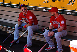 OAKLAND, CA - APRIL 13:  Mike Trout #27 of the Los Angeles Angels of Anaheim sits in the dugout wearing black and gold Nike batting gloves in honor of Kobe Bryant's retirement with Johnny Giavotella #12 before the game against the Oakland Athletics at the Coliseum on April 13, 2016 in Oakland, California. (Photo by Jason O. Watson/Getty Images) *** Local Caption *** Mike Trout; Johnny Giavotella