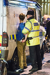 """© Licensed to London News Pictures . 15/12/2012 . Manchester , UK . A policeman detains a man . Revellers enjoy a wet but busy night out on one of the last weekends before Christmas , a traditionally busy time when office parties and clubbers decent on bars and clubs , often known as """" Mad Friday """" . Photo credit : Joel Goodman/LNP"""