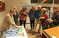 Susy Jones (left) demonstrates her technique for cutting squares of cloths for quilts during a reception for the Art Quilt Exhibit at The Carl & Mary Koehler History Center, 615 1st Ave SE in Cedar Rapids on Saturday morning, March 3, 2012. Jones is a volunteer at the History Center. (Stephen Mally/Freelance)