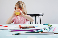 Girl (3-4) drinking orange juice crayons in foreground