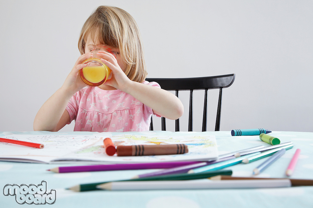 Girl (3-4) drinking orange juice crayons in foreground