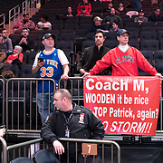 """January 9, 2018, New York, NY : Sal DeRicco, from West Harrison NY, in red, holds up a sign reading """"Coach M, WOODEN it be nice TOP Patrick, again? GO STORM!!"""" as he waits for the start of Tuesday night's matchup between the Hoyas and Red Storm at the Garden. In something of a rematch of their 1985 contest, Basketball greats Patrick Ewing and Chris Mullin returned to Madison Square Garden on Tuesday night to face off as coaches with their respective Georgetown and St. John's teams.  CREDIT: Karsten Moran for The New York Times"""