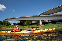 North America, United States, Washington, Bellevue, man and son (age 6) kayaking under highway bridge in Mercer Slough Nature Park.  MR