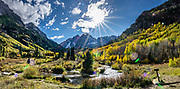 Sunburst over yellow aspen in Maroon Bells-Snowmass Wilderness of White River National Forest, near Aspen, Colorado, USA. The Maroon Bells are two adjacent peaks of the Elk Mountains: Maroon Peak 14,163 feet on left, seen behind North Maroon Peak 14,019 feet. The mountains are on the border between Pitkin County and Gunnison County.