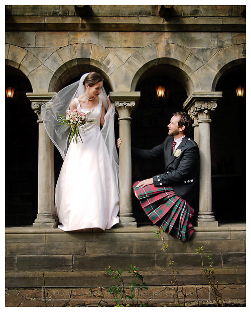 Wedding couple between pillars at the cloisters of Paisley Abbey.
