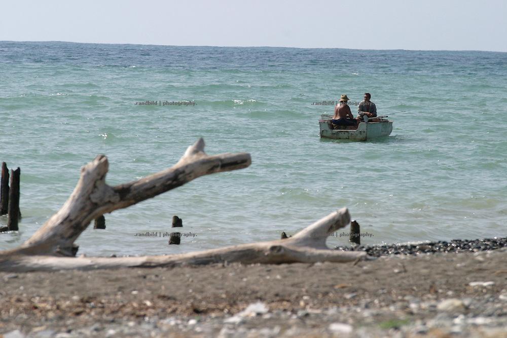 Georgien/Abchasien, Suchumi, 2006-08-30, Zwei Fischer in einem Boot in Küstennähe in Suchumi. Abchasien erklärte sich 1992 unabhängig von Georgien. Nach einem einjährigen blutigen Krieg zwischen den Abchasen und Georgiern besteht seit 1994 ein brüchiger Waffenstillstand, der von einer UNO-Beobachtermission unter personeller Beteiligung Deutschlands überwacht wird. Trotzdem gibt es, vor allem im Kodorital immer wieder bewaffnete Auseinandersetzungen zwischen den Armee der Länder sowie irregulären Kämpfern.  (Two fishermen in his boat near the coastline of Sokhumi. Abkhazia declared itself independent from Georgia in 1992. After a bloody civil war a UNO mission observing the ceasefire line between Georgia and Abkhazia since 1994. Nevertheless nearly every day armed incidents take place in the Kodori gorge between the both armys and unregular fighters )