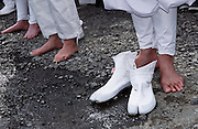 Lay priests take off their tabi footwear to prepare to walk across the embers of a large bonfire of ceder branches in the Hi Watari, fire walking, festival of Takao san Guchi near Tokyo, Japan. Sunday March 11th 2007