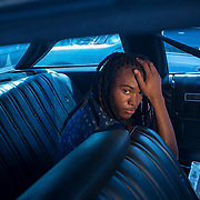 A 17-year-old African American teenager sits in the backseat of a Chevy Impala. The car was abandoned in a junkyard in Rocky Mount, NC.