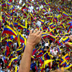 A woman holds up a rosary against the backdrop of hundreds of thousands of Venezuelans marching on the highwayss of Caracas, Venezuela,  Dec. 14, 2002. Opposition marchers are calling for the resignation of President Hugo Chavez and Venezuela is in the grips of a crippling general strike.