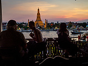 "06 MARCH 2019 - BANGKOK, THAILAND:  Tourists watch the sunset on Wat Arun. Wat Arun Ratchawararam Ratchawaramahawihan or Wat Arun (""Temple of Dawn"") is a Buddhist temple (wat) in Bangkok on the Thonburi side of the Chao Phraya River. The temple derives its name from the Hindu god Aruna, who is personified as the rising sun. Wat Arun is among the best known of Thailand's temples. The temple has existed since at least the seventeenth century, but its distinctive prang (spires) were built in the Khmer style in the early nineteenth century during the reign of King Rama II.  PHOTO BY JACK KURTZ"