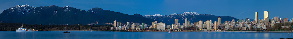 Wide panorama of Vancouver's English Bay. From the anchored M.V. Edgewater Fortune in front of Stanley Park to the West End condo and apartment towers, the Empire Landmark Hotel and the new Trump Tower and Living Shangri-La towers. Mountains in the background are Crown and Grouse (left) and Mount Seymour (right).  Photographed from Kitsilano Beach Park in Vancouver, British Columbia, Canada.  Full resolution file is 36203 x 4919 pixels.