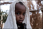 """Buzunesh, 5 years old, is being married, with a young boy, 1 year older. In some cultures, arranged marriage is a tradition handed down through many generations. Parents who take their son or daughter's marriage into their own hands have themselves been married by the same process. Child marriages are typically made for economic or political reasons. North West of Ethiopia, on monday, Febrary 16 2009.....In a tangled mingling of tradition and culture, in the normal place of living, in a laid-back attitude. The background of Ethiopia's """"child brides"""", a country which has the distinction of having highest percentage in the practice of early marriages despite having a law that establishes 18 years as minimum age to get married. Celebrations that last days, their minds clouded by girls cups of tella and the unknown for the future. White bridal veil frame their faces expressive of small defenseless creatures, who at the age ranging from three to twelve years shall be given to young brides men adults already...To protect the identities of the recorded subjects names and specific places are fictional."""