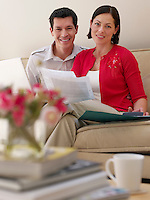 Couple using laptop  and holding documents sitting on sofa  portrait