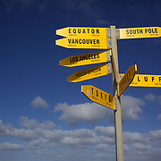 The signpost at the Cape Reinga Lighthouse at the north western most tip of the Aupouri Peninsula, at the northern end of the North Island of New Zealand. . Cape Reinga is  a favourite tourist attraction and the meeting point  between the Tasman Sea to the west and the Pacific Ocean to the east. From the lighthouse it is possible to watch the tidal race, as the two seas clash to create unsettled waters just off the coast. Cape Reinga, North Island, New Zealand, 21st November 2010. Photo Tim Clayton.