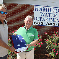Hamilton Water Department Manager/Operator Robert Pounders, left, accepts an American flag from Buzzy Cullum on behalf of American Legion Post 26. The legion donates flags to schools, churches, cemeteries, nonprofits and public water districts. Auxiliary Unit 26 is working on a project to provide a permanent firepit to burn worn out flags.