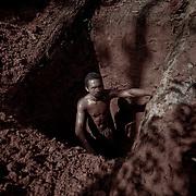 Brasile, Amazzonia, garimpo de Juma. Le miniere a cielo aperto del garimpo de Juma, dove la vita dei minatori scorre tra pericolo per un lavoro al limite e deforestazione incontrollata. Aspettando di trovare l'oro che cambi la loro vita. In questa foto un minatore scava una buca per analizzare la terra in cerca di oro e capire se procedere ulteriormente. Brazil, Amazonia, garimpo de Juma. The open pit mines of garimpo de Juma, where the miners work flows between danger and uncontrolled deforestation. Waiting to find the gold that changes their lives. In this picture a miner digs a hole to analyze the land in search of gold and whether to proceed further.
