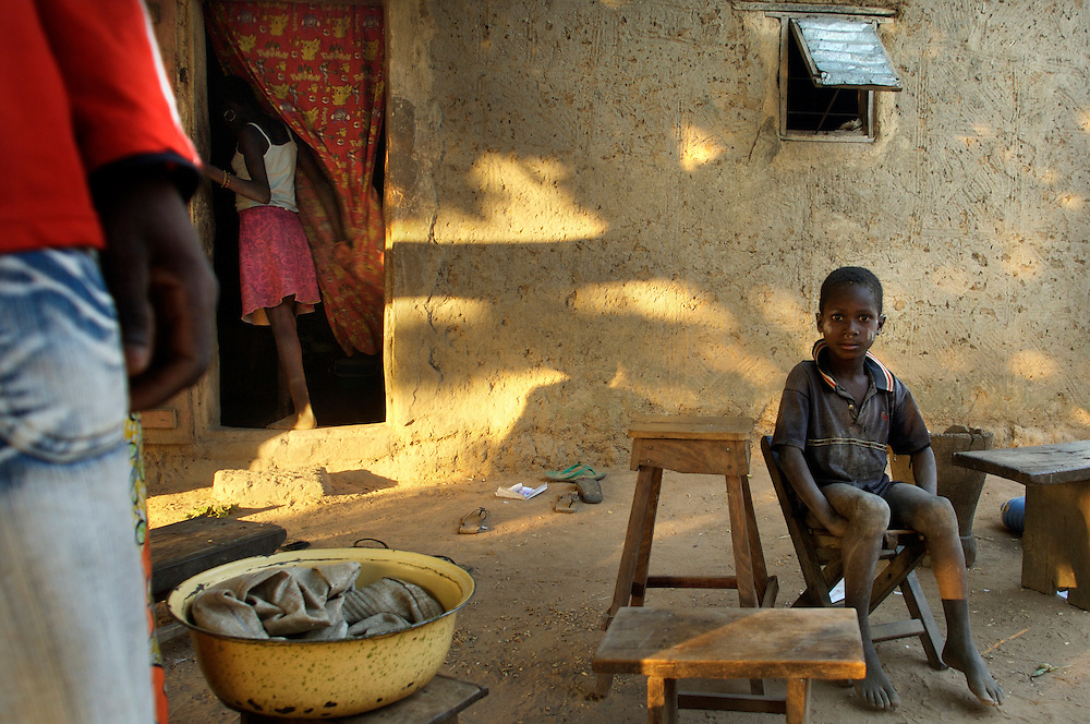 Natitingou December 2006 - A boy sits in front of his house in Natitingou, Benin.  The home is built in the Tata Somba architectural style. © Jean-Michel Clajot