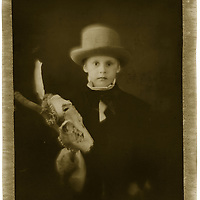 A young boy wearing a top hat holding a skull