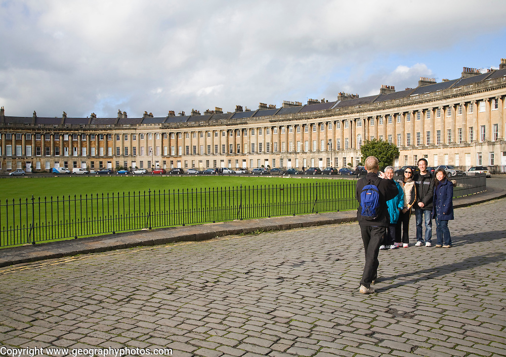 Asian tourist family pose for a photograph, The Royal Crescent, architect John Wood the Younger built between 1767 and 1774, Bath, Somerset, England
